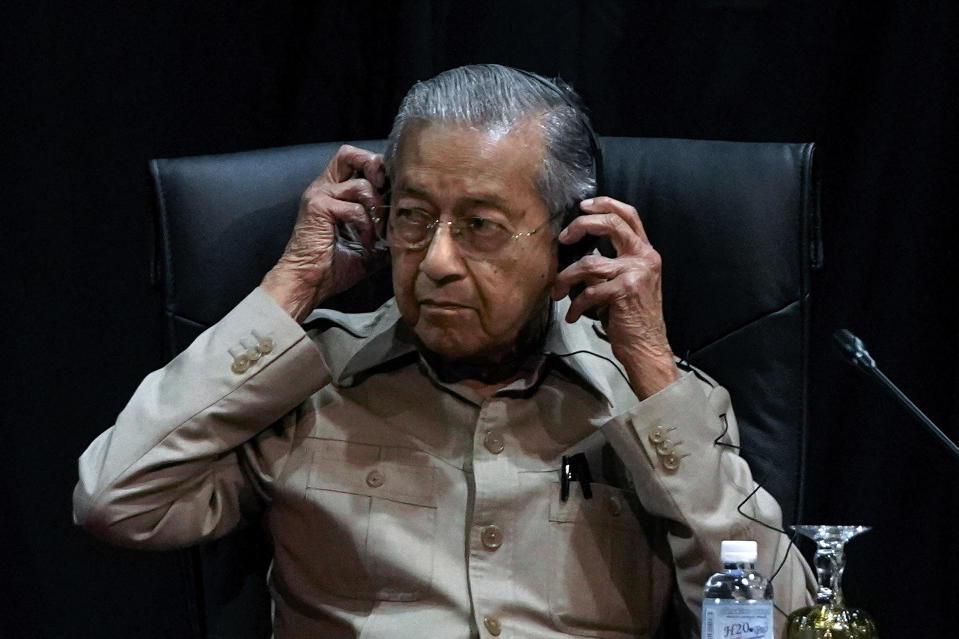 Malaysia's interim leader Mahathir Mohamad adjusts his headphone as he attends the committee on the exercise of the inalienable rights of the Palestinian people, in Kuala Lumpur, Malaysia, Friday, Feb. 28, 2020. The speaker of Malaysia's House rejected Mahathir Mohamad's call for a vote next week to chose a new premier, deepening the country's political turmoil after the ruling alliance collapsed this week. (AP Photo/Vincent Thian)