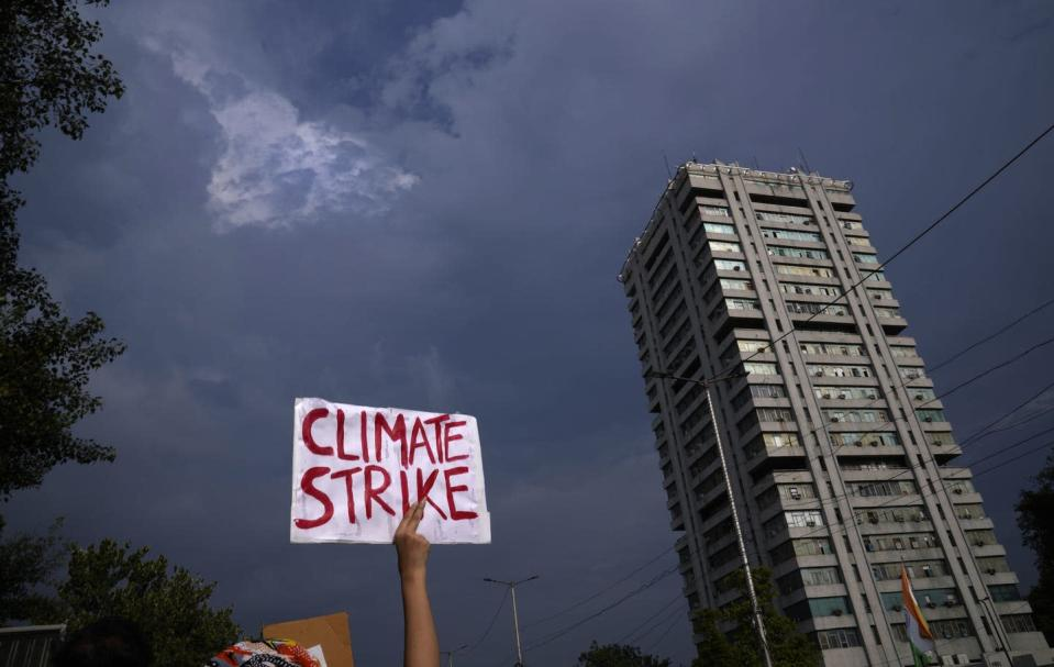 """<span class=""""caption"""">A protestor holds a banner at the Fridays for Future march in New Delhi on Sept. 24, 2021. </span> <span class=""""attribution""""><span class=""""source"""">(AP Photo/Manish Swarup) </span></span>"""