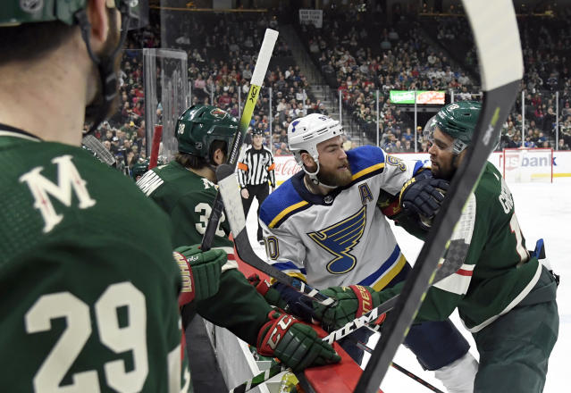 St. Louis Blues' Ryan O'Reilly (90) and Minnesota Wild's Jordan Greenway (18) shove each other in front of the Minnesota Wild bench after a whistle during the second period of an NHL hockey game Sunday, Feb. 23, 2020, in St. Paul, Minn. (AP Photo/Hannah Foslien)