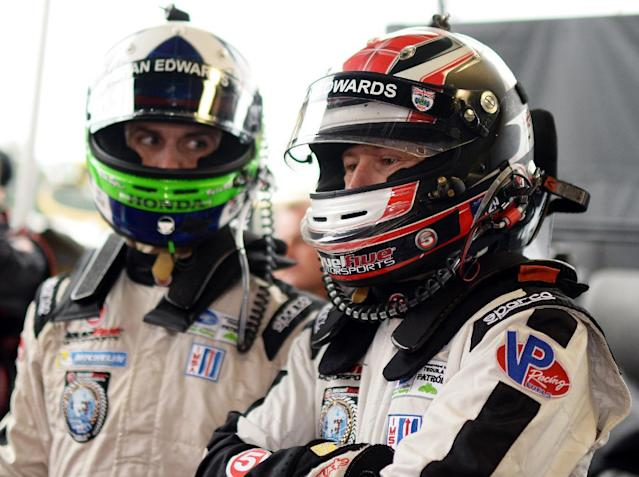 Drivers Marino Franchitti, left, of Scotland, and Ryan Briscoe, of Australia, talk while they wait for a pit stop during the warm up session for the American Le Mans Series' Petit Le Mans auto race at Road Atlanta, Saturday, Oct. 19, 2013, in Braselton, Ga. (AP Photo/Rainier Ehrhardt)