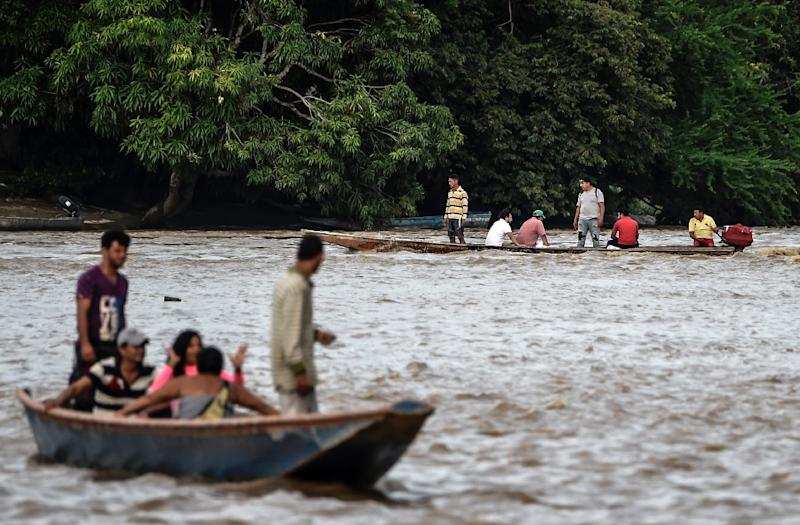 Venezuelans take boats from one muddy shore to the other to buy supplies from Colombia or journey onwards (AFP Photo/Juan BARRETO)