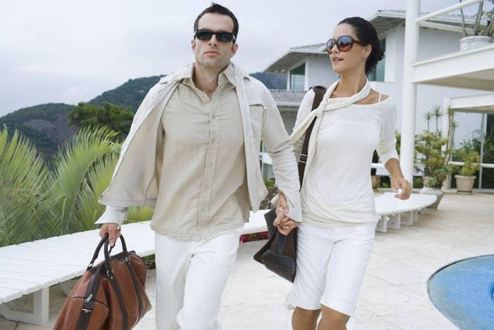 A wealthy couple walk hand-in-hand by a pool