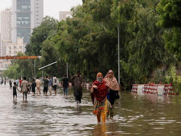 People wade through a flooded road after the monsoon rain, as the outbreak of the coronavirus disease (COVID-19) continues, in Karachi.