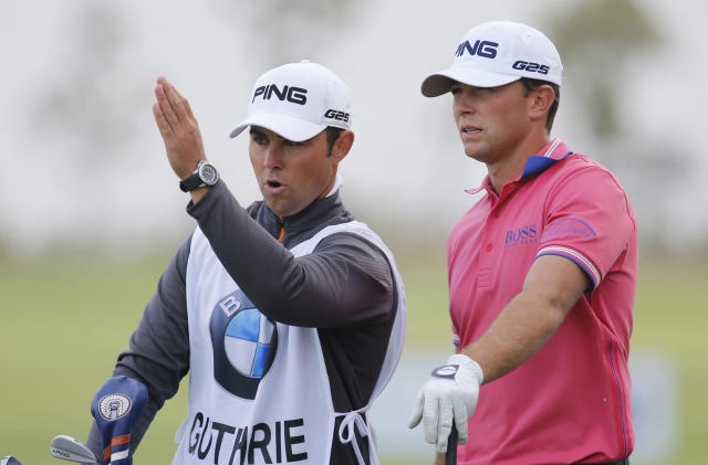 Early leader Luke Guthrie of the U.S., right, listens to his caddie before teeing off at the 8th hole during the second round of the BMW Masters golf tournament at the Lake Malaren Golf Club in Shanghai, China, Friday, Oct. 25, 2013. (AP Photo/Eugene Hoshiko)