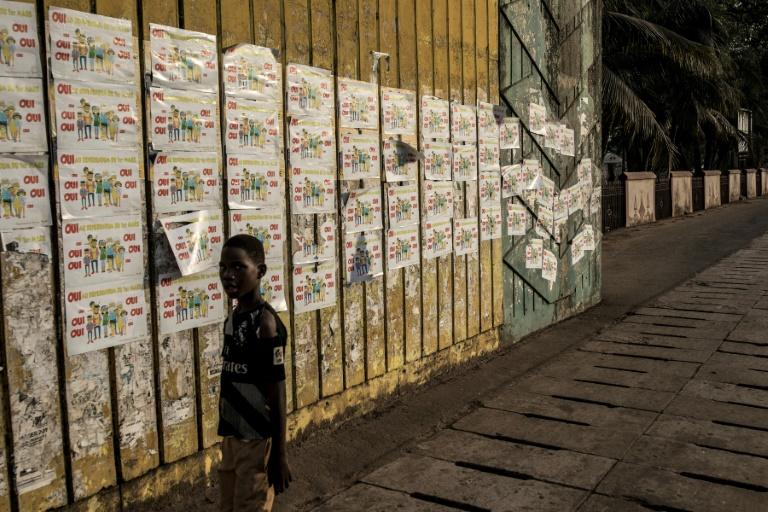 A boy walks past a wall plastered with posters to vote 'Yes' in Sunday's referendum (AFP Photo/JOHN WESSELS)