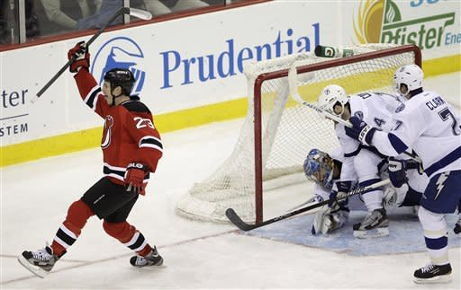 New Jersey Devils' David Clarkson, left, celebrates after scoring against Tampa Bay Lightning goalie Dwayne Roloson, Brett Connolly and Brett Clark in the third period of an NHL hockey game, Thursday, March 29, 2012, in Newark, N.J. The Devils won 6-4. (AP Photo/Julio Cortez)