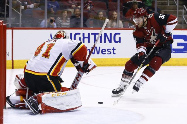 Arizona Coyotes right wing Christian Fischer (36) tries to get off a shot on Calgary Flames goaltender Mike Smith (41) during the second period of an NHL hockey game Monday, March 19, 2018, in Glendale, Ariz. (AP Photo/Ross D. Franklin)