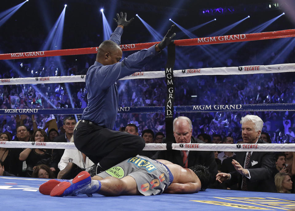 Referee Kenny Bayless signals the end of the match for Manny Pacquiao, who was knocked out by Juan Manuel Márquez in the sixth round on Saturday, Dec. 8, 2012 in Las Vegas. (AP/Julie Jacobson)