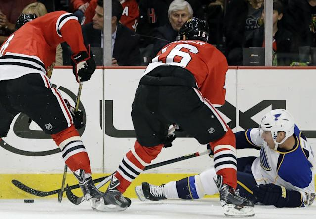 St. Louis Blues' Derek Roy (12), right, controls the puck against Chicago Blackhawks' Nick Leddy (8) and Marcus Kruger (16) during the first period of an NHL hockey game in Chicago, Thursday, Oct. 17, 2013. (AP Photo/Nam Y. Huh)