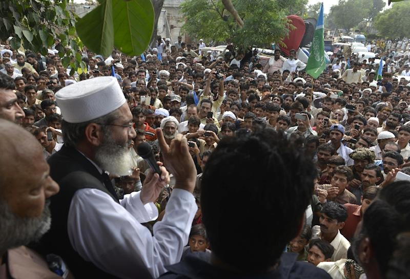 Siraj ul Haq (L), leader of Jamaat-e-Islami' party, addresses the villagers in Hussain Khanwala village, some 55 kms southwest of Lahore on August 9, 2015, after a massive child abuse scandal in their village (AFP Photo/Arif Ali)
