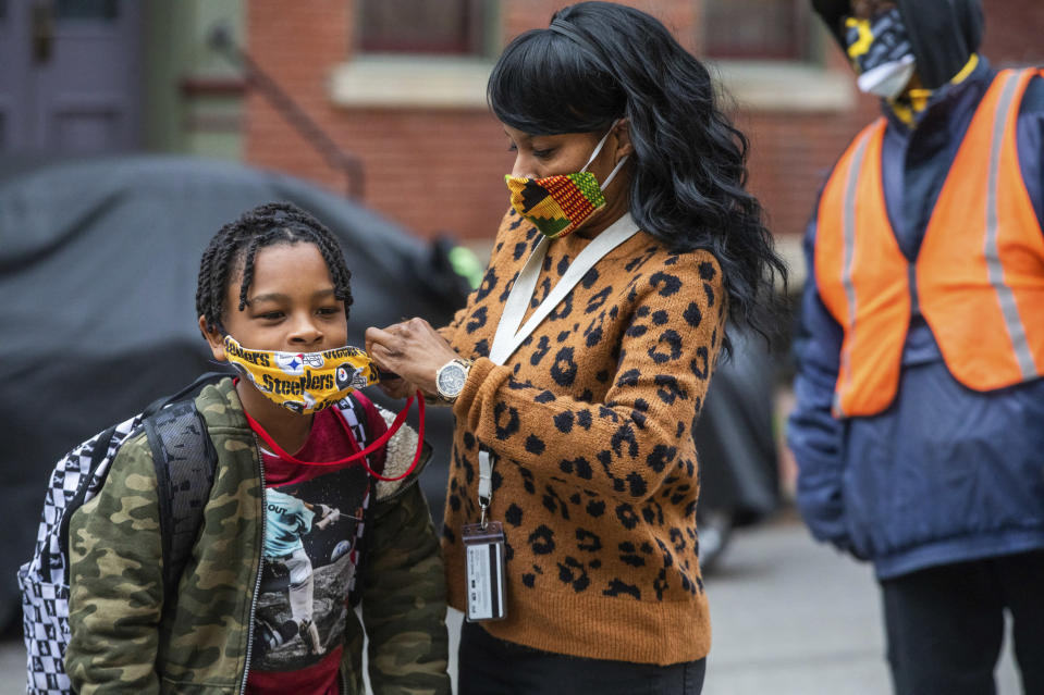 FILE - In this Monday, March 29, 2021, file photo, Jenea Edwards, of the North Side, helps her son Elijah, 9, in the third grade, with his mask before heading into Manchester Academic Charter School on the first day of in-person learning via a hybrid schedule, in Pittsburgh. A new survey from the Biden administration finds that large numbers of students are not returning to the classroom even as more schools reopen for full-time, in-person learning. (Andrew Rush/Pittsburgh Post-Gazette via AP, File)