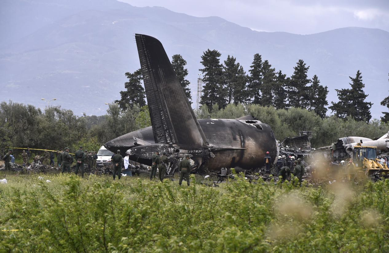 <p>Rescuers are seen around the wreckage of an Algerian army plane which crashed near the Boufarik airbase from where the plane had taken off on April 11, 2018. (Photo: Farouk Batiche/Anadolu Agency/Getty Images) </p>