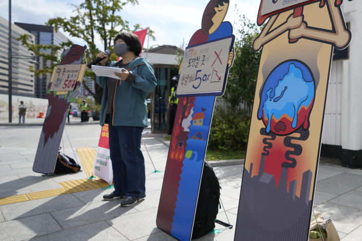 """An environmental activist speaks during a press conference on the effort to curb greenhouse gas emissions as part of the climate strike in Seoul, South Korea, Friday, Sept. 24, 2021. The banners read: """"Greenhouse gas, 50 percent down."""" (AP Photo/Lee Jin-man)"""