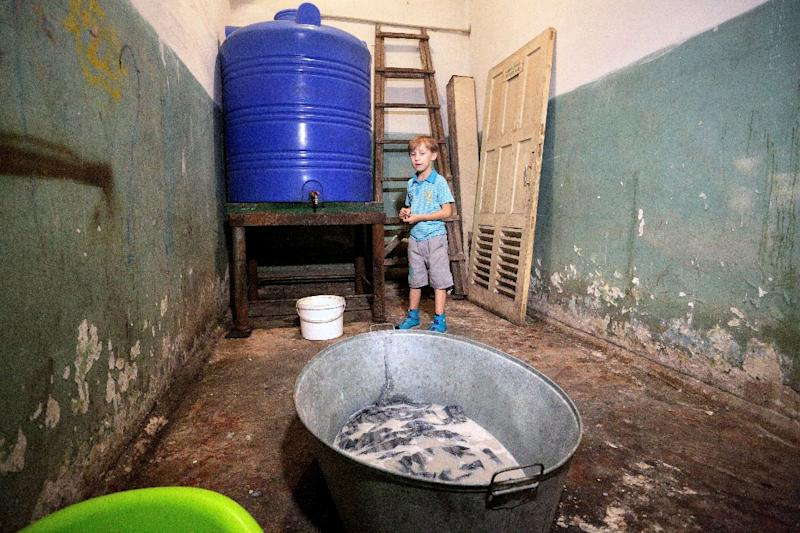 Sasha, 10, stands in a bomb shelter in Donetsk, eastern Ukraine, on September 19, 2016, where he hides with his mother Elena