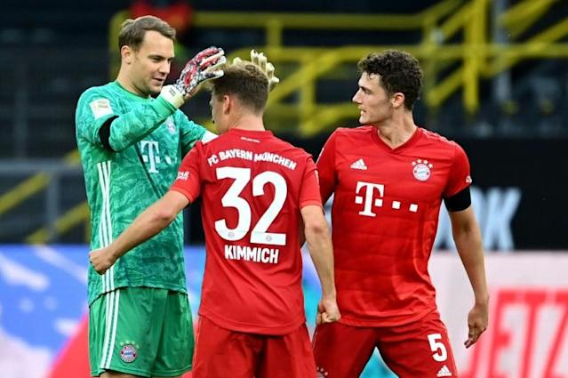 Joshua Kimmich is congratulated by Bayern Munich goalkeeper Manuel Neuer after scoring the winner against Dortmund and effectively ending the title race (AFP Photo/Federico GAMBARINI)