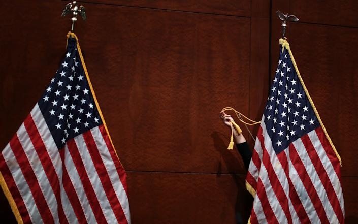 A House Judiciary Committee staff member adjusts flags before U.S. Attorney General William Barr testifies in the Congressional Auditorium at the U.S. Capitol Visitors Center July 28, 2020 in Washington, DC - GETTY IMAGES