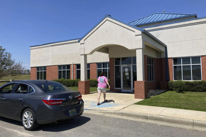 A woman walks into Family Medical Associates, which is encouraging patients to get COVID-19 vaccines, in Haleyville, Ala., Monday, April 5, 2021. The clinic is located in Winston County, which is trying to get more people immunized but is running into problems with both supply and willingness from a population that is both nearly all white and voted heavily for former President Donald Trump last year. (AP Photo/Jay Reeves)