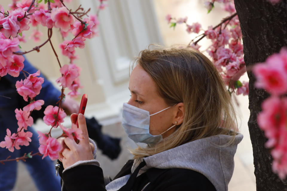 A woman wearing a face mask to help curb the spread of the coronavirus takes photo of fake flowers at the GUM, the State Department store, near Red Square in Moscow, Russia, Thursday, June 10, 2021. The Russian authorities reported a spike in coronavirus infections on Thursday, with new confirmed cases exceeding 11,000 for the first time since March. (AP Photo/Alexander Zemlianichenko)