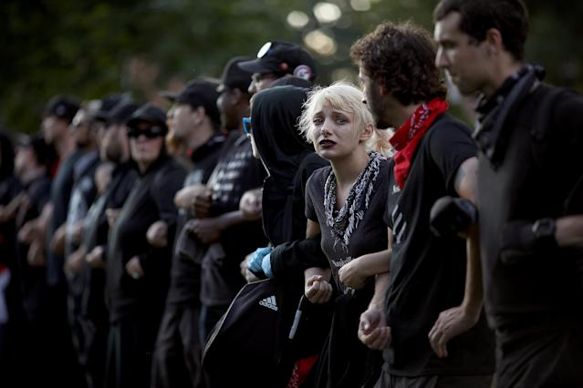 "<p>Protesters with a group known as ""Antifa"", or anti-fascists, link arms at an event on the campus of the University of Virginia organized by the group Students Act Against White Supremacy marking the one year anniversary of a deadly clash between white supremacists and counter protesters August 11, 2018 in Charlottesville, Virginia. Charlottesville has been declared in a state of emergency by Virginia Gov. Ralph Northam as the city braces for the one year anniversary of the deadly clash between white supremacist forces and counter protesters over the potential removal of Confederate statues of Robert E. Lee and Stonewall Jackson. A 'Unite the Right' rally featuring some of the same groups is planned for tomorrow in Washington, DC. (Photo: Win McNamee/Getty Images) </p>"