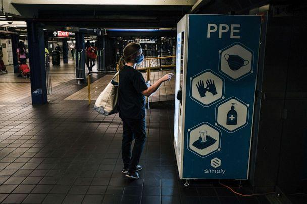 PHOTO: A woman uses a personal protective equipment vending machine that was recently deployed by the Metropolitan Transportation Authority in the 42nd Street Port Authority Bus Terminal subway stop on June 30, 2020, in New York. (Byron Smith/Getty Images)