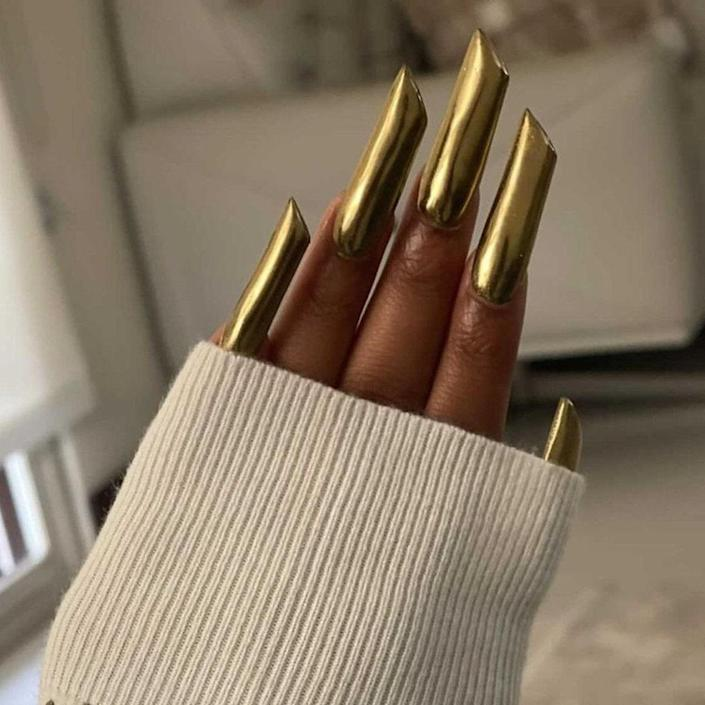 """A metallic manicure in one solid color is sure to turn heads. Jamaica-based nail artist <a href=""""https://www.instagram.com/nail_it_malli/"""" rel=""""nofollow noopener"""" target=""""_blank"""" data-ylk=""""slk:Carrie Anna Malcolm"""" class=""""link rapid-noclick-resp"""">Carrie Anna Malcolm</a> used a gold chrome powder to create these lipstick nails. First, she painted on a black gel polish and <a href=""""https://www.allure.com/gallery/best-top-coat-nail-polish?mbid=synd_yahoo_rss"""" rel=""""nofollow noopener"""" target=""""_blank"""" data-ylk=""""slk:topcoat"""" class=""""link rapid-noclick-resp"""">topcoat</a>, and then she added the metallic powder, sealing the whole look with topcoat once again."""