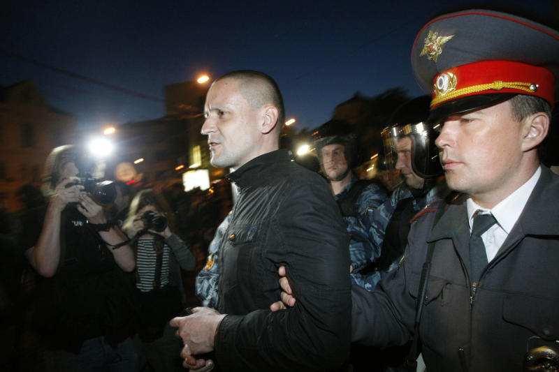 CORRECTS SPELLING OF SERGEI - Russian police officers detain opposition leader Sergei Udaltsov while protesters gather near the presidential administrations building in downtown Moscow early Tuesday, May 8, 2012, a day after Putin's inauguration. Vladimir Putin took the oath of office in a brief but regal Kremlin ceremony on Monday, while on the streets outside thousands of helmeted riot police prevented hundreds of demonstrators from protesting his return to the presidency. (AP Photo/Alexander Zemlianichenko Jr )