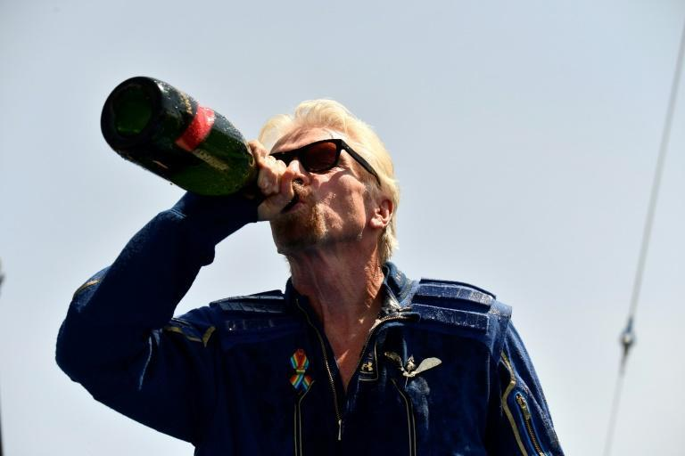 Virgin Galactic founder Richard Branson drinks champagne after his space flight