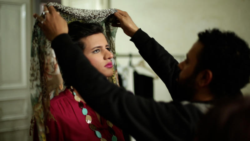 """In this undated image made from video released by the producers of """"Awel el Kheit"""" or """"the Thread"""" which airs on the private TV station ONTV, a crew member puts a woman's headscarf on Waleed Hammad before setting out on the streets of Cairo, Egypt, dressed as a woman for a an investigative story on sexual harassment. The 24-year-old actor dressed conservatively for his mission into the secret world of sexual harassment and abuse on the streets of Cairo, donning a long skirt and sleeved shirt and covering his head like many Egyptian women.(AP Photo)"""