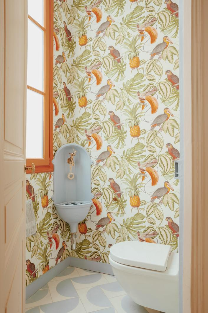 This corner of the bathroom feels like a tropical paradise, with tiles by Popham Design alongside Paradiso wallpaper by Erismann.