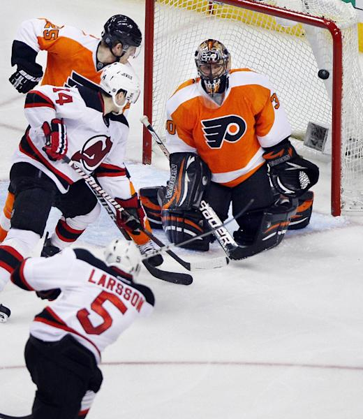New Jersey Devils' Adam Larsson, front, sends the puck into the net past Philadelphia Flyers' Ilya Bryzgalov to tie the game during the third period in Game 2 of an NHL hockey Stanley Cup second-round playoff series, Tuesday, May 1, 2012, in Philadelphia. The Devils won 4-1 tying the best of seven series at 1-1. Looking on are Devils' Adam Henrique (14) and Flyers' Matt Carle (25). (AP Photo/Tom Mihalek)