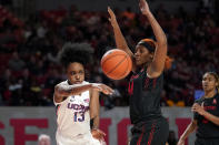 Connecticut's Christyn Williams (13) passes the ball as Houston's Jazmaine Lewis (44) defends during the second half of an NCAA college basketball game Saturday, Feb. 29, 2020, in Houston. Connecticut won 92-40. (AP Photo/David J. Phillip)