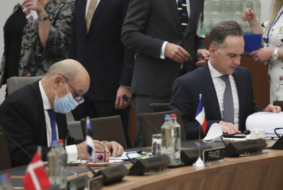 German Foreign Minister Heiko Maas, right, looks at his papers next to his French counterpart Jean-Yves Le Drian during a NATO foreign ministers meeting at NATO headquarters in Brussels, Tuesday, March 23, 2021. (Yves Herman, Pool via AP)