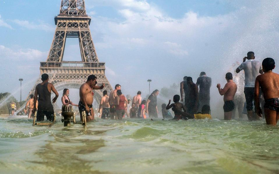 People cool down in the fountains of the Trocadero gardens in Paris - AP