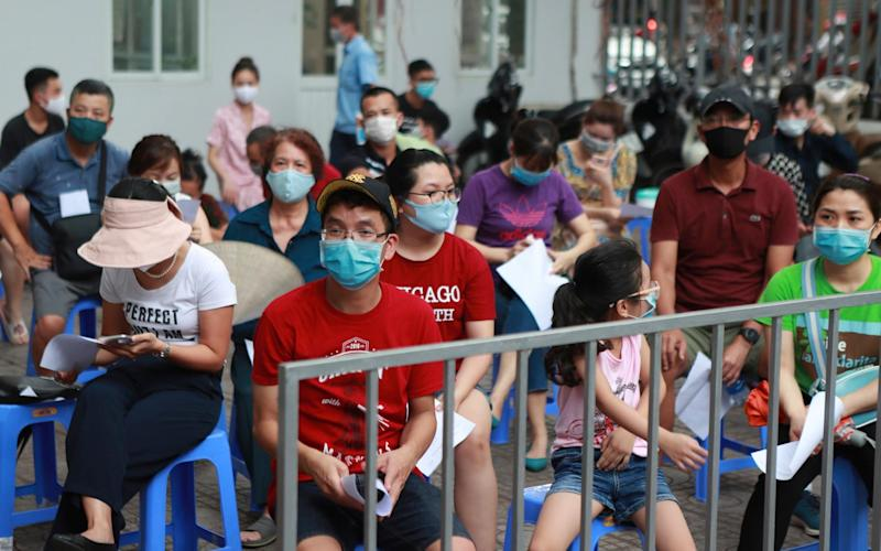 People wait in line in Hanoi for Covid-19 tests - Hau Dinh/AP