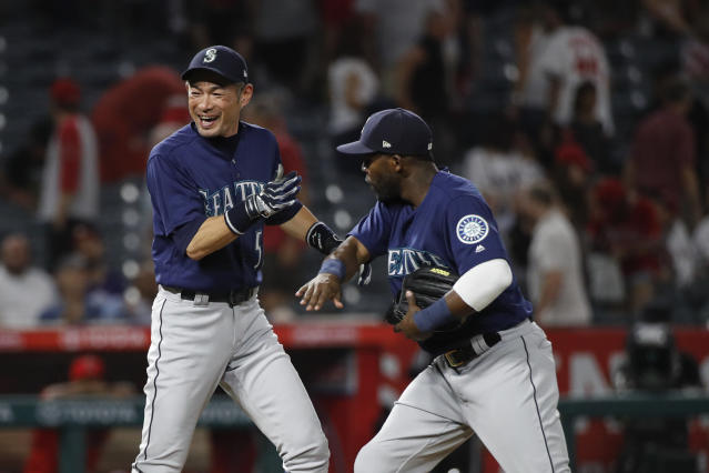 Seattle Mariners' Ichiro Suzuki, left, and Guillermo Heredia celebrate the team's 3-0 win against the Los Angeles Angels in a baseball game Wednesday, July 11, 2018, in Anaheim, Calif. (AP Photo/Jae C. Hong)