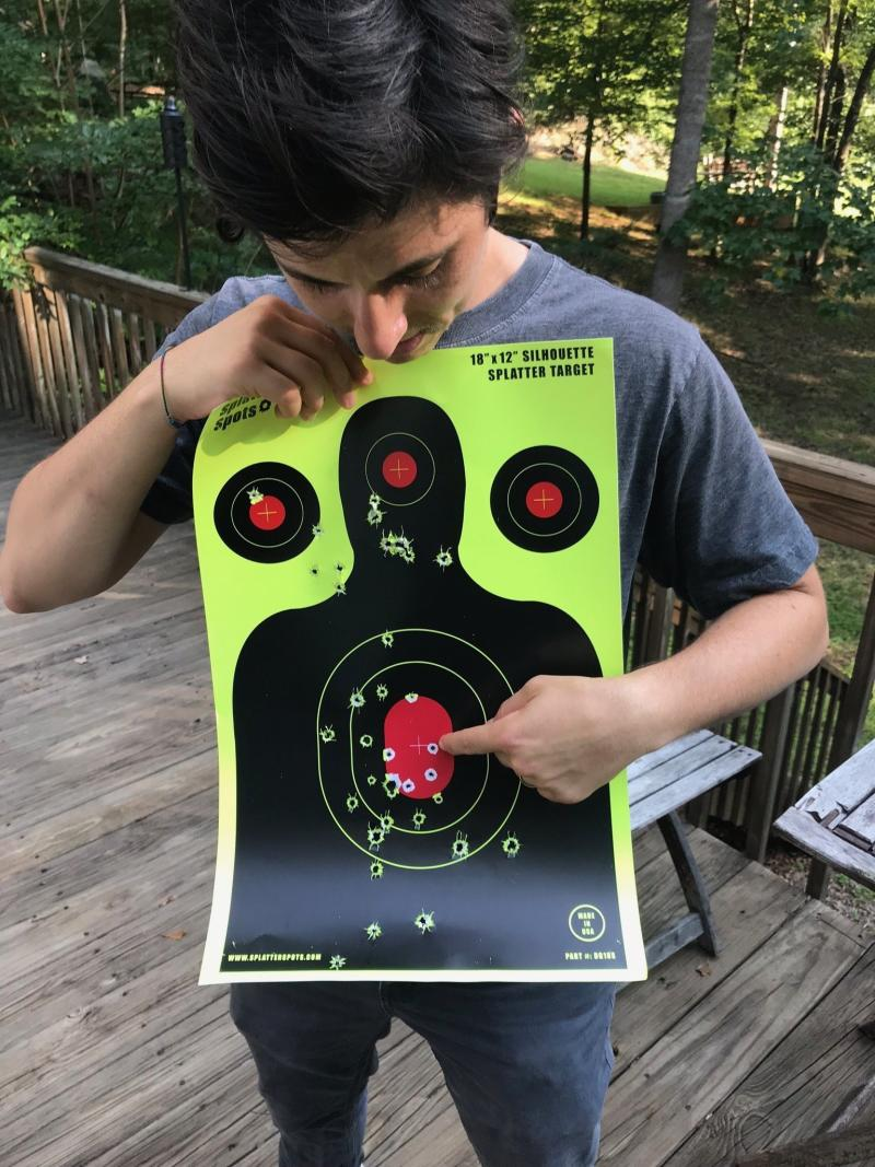 Mel Plaut pointing out the first shot they ever took, a bullseye with a .22 (hence the tiny hole), in August 2018.