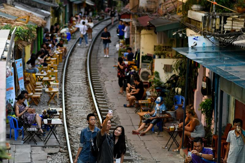 This photograph taken on June 9, 2019 shows a family posing for a selfie on the railway track in Hanoi's popular train street. (Photo by Manan VATSYAYANA / AFP) (Photo credit should read MANAN VATSYAYANA/AFP/Getty Images)