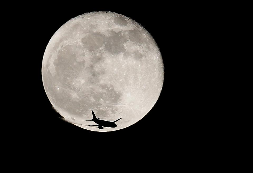 FILE PHOTO: An airplane is silhouetted against a full moon in the sky over London January 1, 2010. REUTERS/Suzanne Plunkett/File Photo