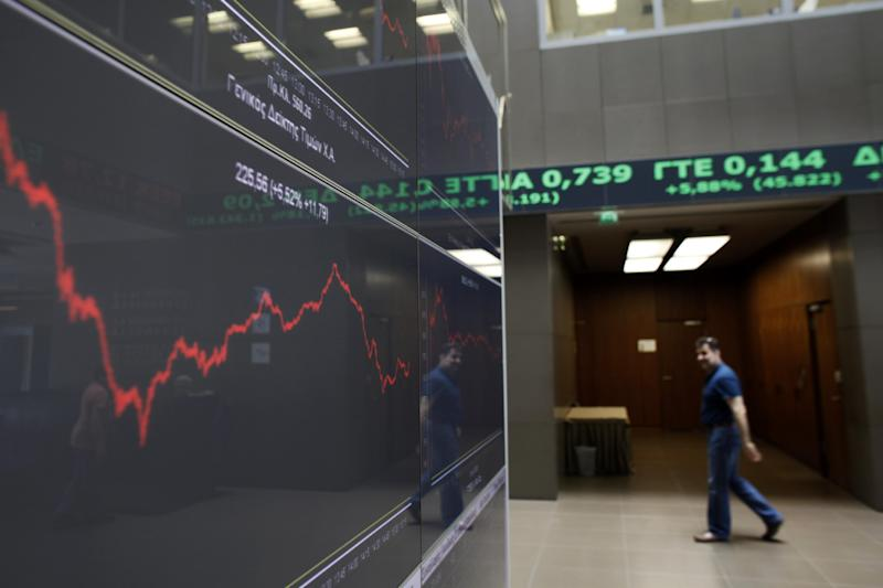 A man walks as above screens showing rising stocks in green as he is reflected in the chart with stock prices at the Greek Stock Exchange in Athens, on Monday , June 18, 2012. In Athens, stocks lost initial strong gains but were still 4.5 percent up in afternoon trading, on the back of strong gains last week that anticipated the conservative victory. (AP Photo/Kostas Tsironis)