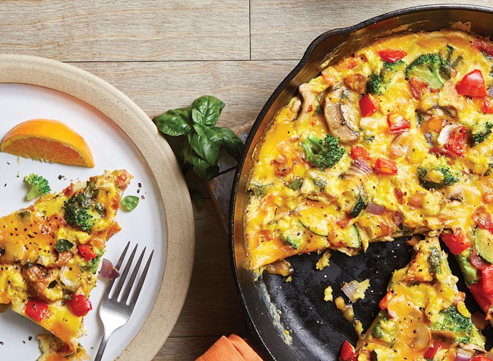 loaded vegetable frittata in cast iron skillet with slice on plate and fork