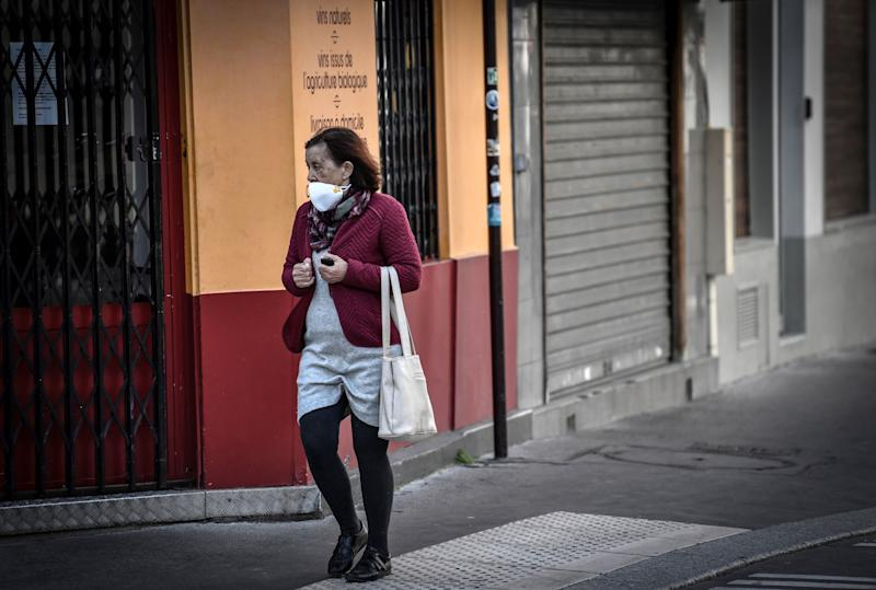 A woman wearing a protective mask carries a bag on March 26, 2020 in Paris, on the tenth day of a lockdown aimed at curbing the spread of the COVID-19 (novel coronavirus) in France. (Photo by STEPHANE DE SAKUTIN / AFP) (Photo by STEPHANE DE SAKUTIN/AFP via Getty Images)