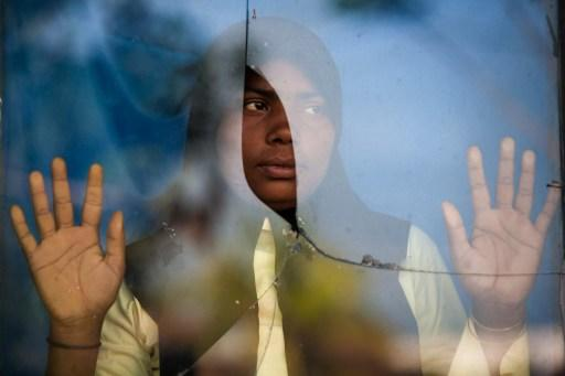 File photo of an ethnic Rohingya refugee who was among a boatload of asylum seekers standing by the window of an immigration quarantine centre in Langsa district in Aceh province. — AFP pic