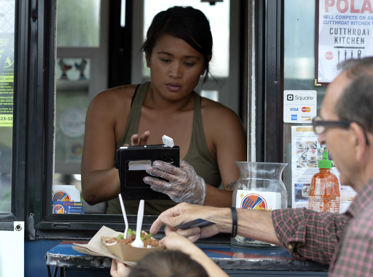 Kathy Poland of Taste of the Philippines swipes uses square system for her transactions June 18, 2015 at Civic Center Park. (Photo By John Leyba/The Denver Post via Getty Images)
