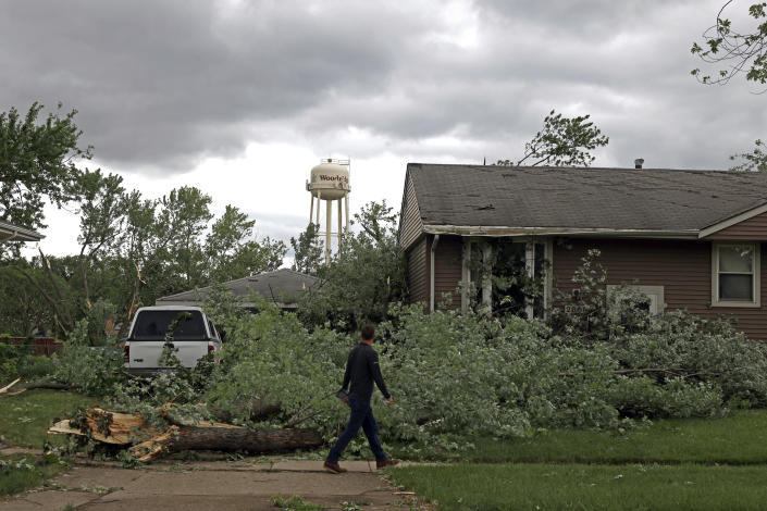 A man walks past a damaged house and tree after a tornado passed through the area on Monday, June 21, 2021, in Woodridge, Ill. (AP Photo/Shafkat Anowar)