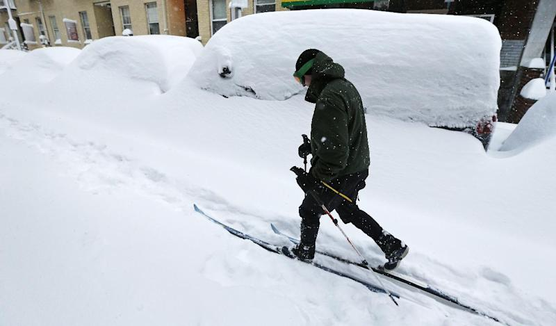Mike Brown, of Boston, cross country skis past snow covered cars through the Chinatown neighborhood of Boston, Saturday, Feb. 9, 2013. The Boston area received about two feet of snow from a winter storm. (AP Photo/Charles Krupa)