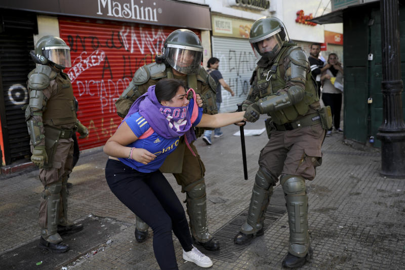 Police grab an anti-government demonstrator in Santiago, Chile, Tuesday, Oct. 29, 2019. Chileans gathered Tuesday for a 12th day of demonstrations that began with youth protests over a subway fare hike and have become a national movement demanding greater socio-economic equality and better public services in a country long seen as an economic success story. (AP Photo/Rodrigo Abd)