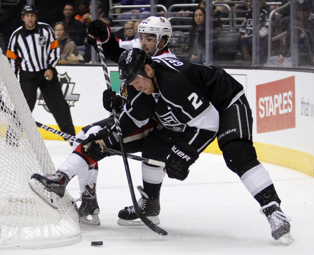 Los Angeles Kings defenseman Matt Greene (2) defends against Ottawa Senators left wing Cory Conacher from getting to the puck behind the net during the first period of their NHL hockey game on Wednesday, Oct. 9, 2013, in Los Angeles. (AP Photo/Alex Gallardo)