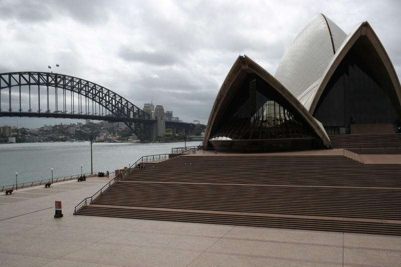 People are seen on the nearly deserted steps of the Sydney Opera House
