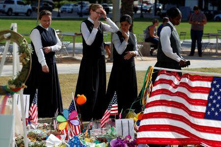 Youths in traditional clothing look at a makeshift memorial for the Pulse nightclub mass shooting victims last week in Orlando, Florida, U.S., June 21, 2016. REUTERS/Carlo Allegri