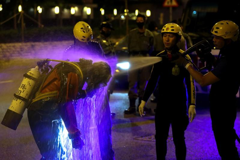 A rescue diver from the Fire Service department is rinsed after entering the sewage system to search anti-government protesters who escaped from the Hong Kong Polytechnic University (PolyU) after being barricaded by police officers